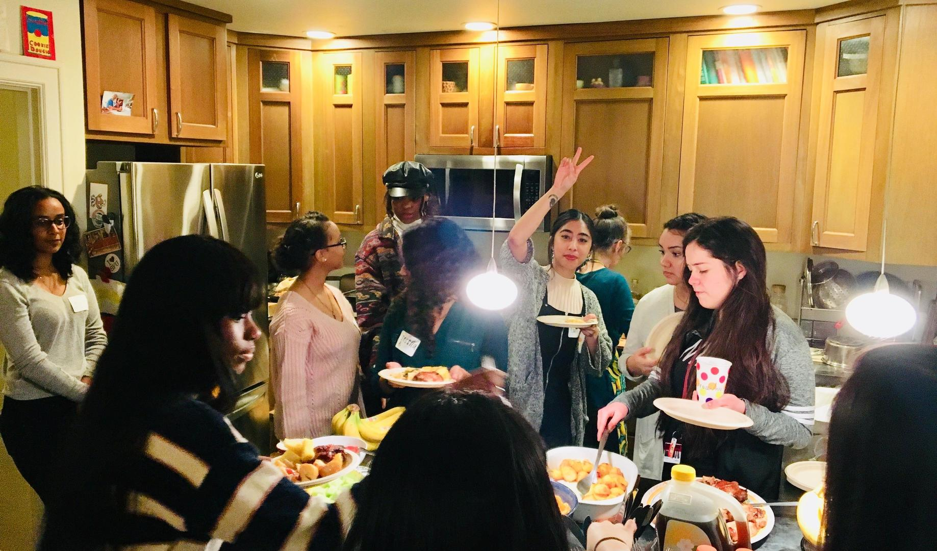 Students and professors crowd in a kitchen to get food from a buffet laid out on the counter.