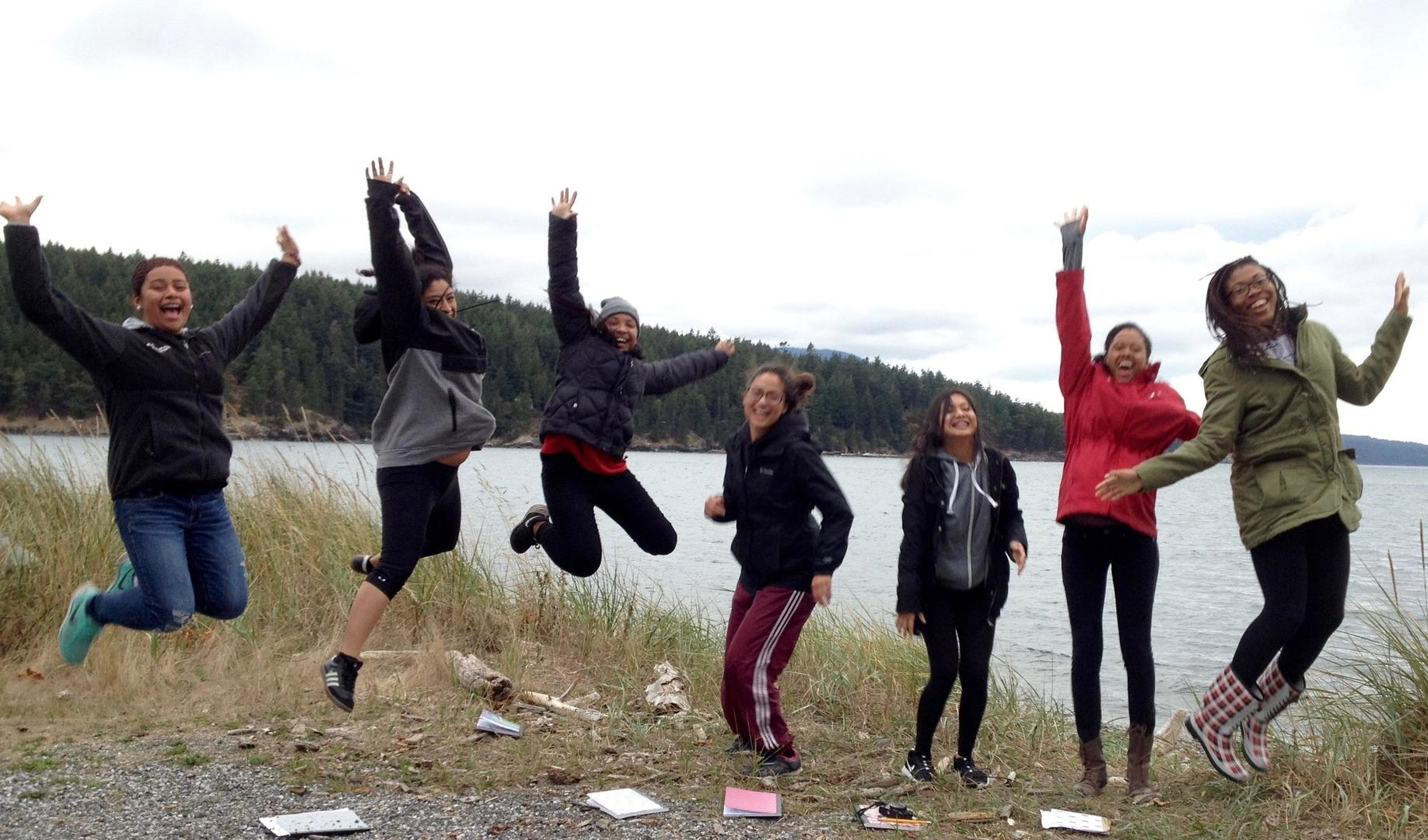 """Five students jump in the hair for a """"High School Musical"""" style pose, two remain on the ground, mid-jump."""