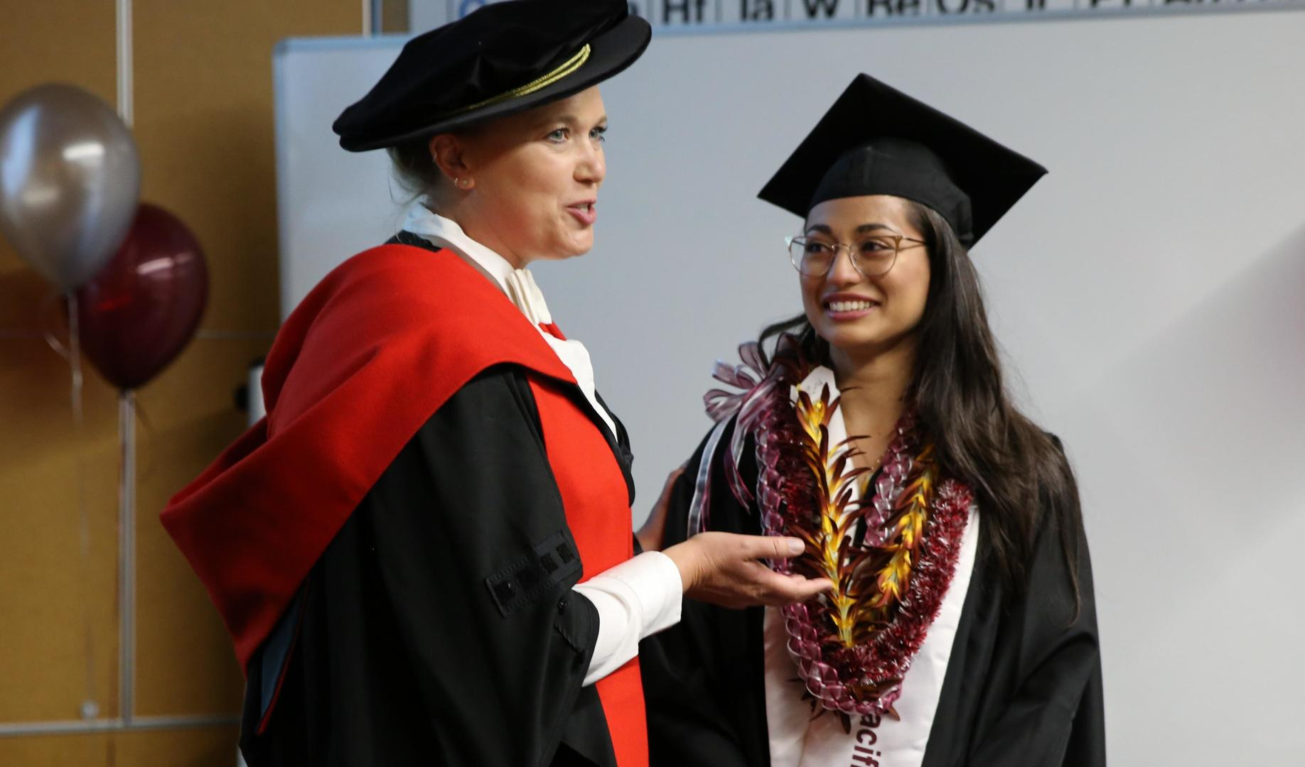 A student in a cap and gown speaks with a professor, who is in academic regalia.