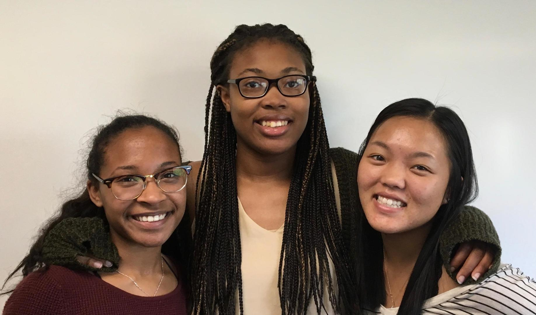 Three students smile and pose for a photo.