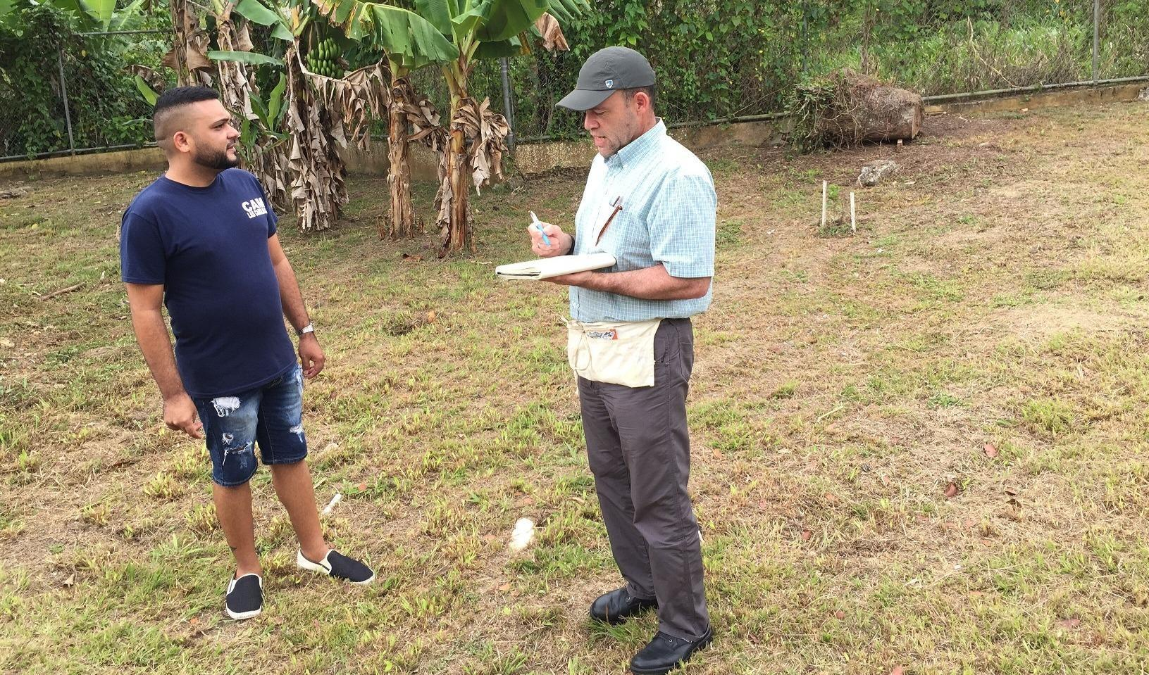 two men standing in a field and talking