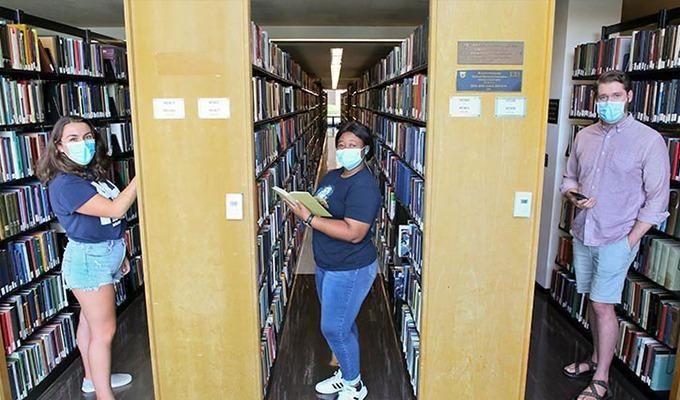 Students stand in the library stacks with masks on.