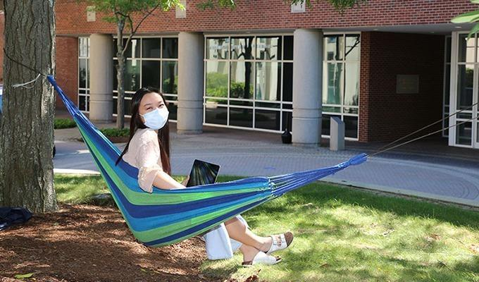 A student sits in a hammock on campus